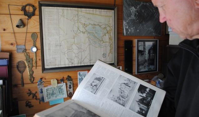 Dick Daniëls bekijkt oude boeken. Elke bezoeker kan zaterdag 12 mei terecht bij een expert op het gebied van zijn meegebrachte spullen. (Foto: Vereniging Oud Linschoten)