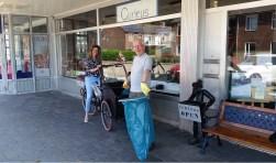 Jessica Schardijn van Zorgbureau Zeeland vol trots op de bakfiets waarmee zwerfafval opgehaald wordt in Paauwenburg. Buurtbewoner Jan van Adrichem geeft vast het goede voorbeeld. FOTO: CONNY DEN HEIJER