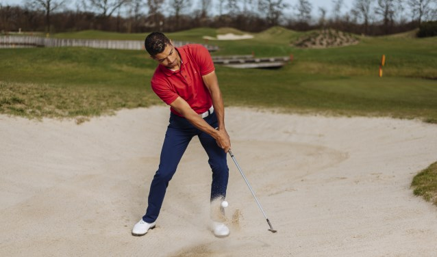 Max Albertus slaat een technisch fraaie bunkerslag om zich te bevrijden uit een 'bunker'. Dat is een soort zandbak, die een hindernis vormt op een golfbaan. Foto: Nick Dors