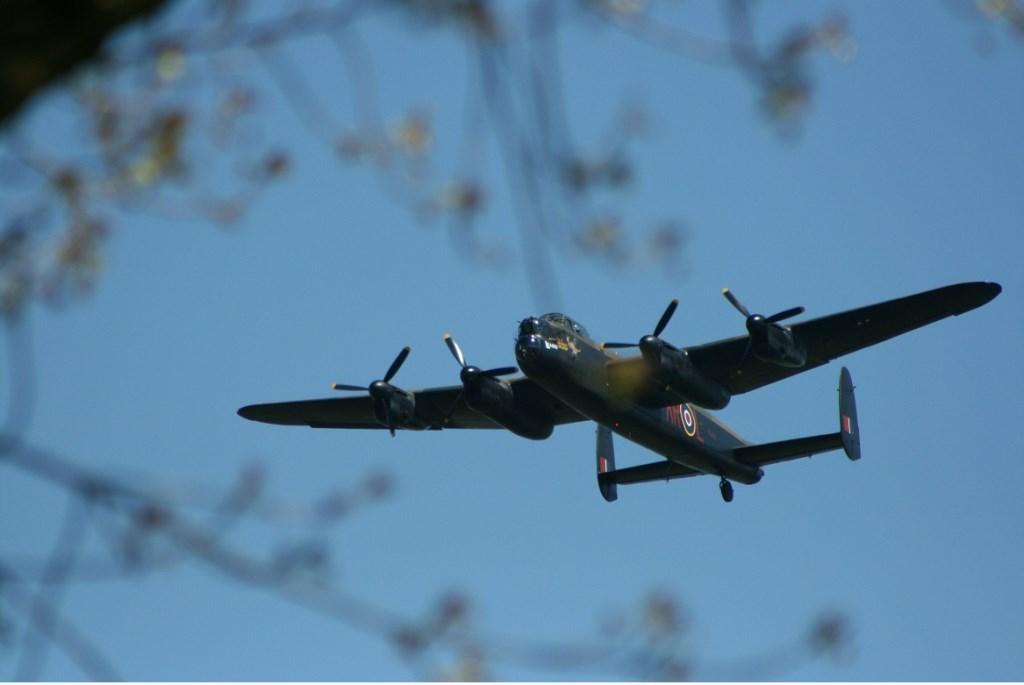 Vanachter het voorjaarsgroen verschijnt de ronkende Lancaster voor een paar rondjes boven de menigte rond Fort Vuren. Foto's: Rob Zantinge
