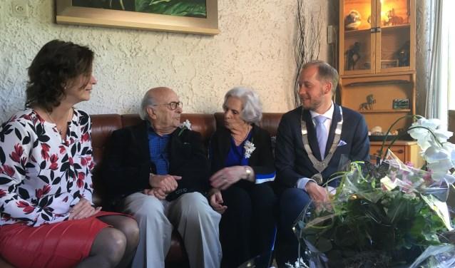 Met op tafel het boeket van de koning, spreken de burgemeester en zijn vrouw gezellig met het jubilerende echtpaar.