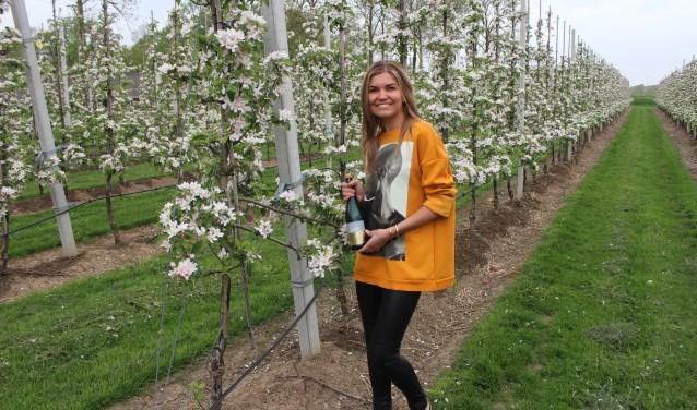 Sally van Ommeren tussen de bloesem, die momenteel ook te zien is bij Gruun in Ommeren, op de plek waar de Liendense Appel Café Gruun runt. (Foto: Henk Jansen)