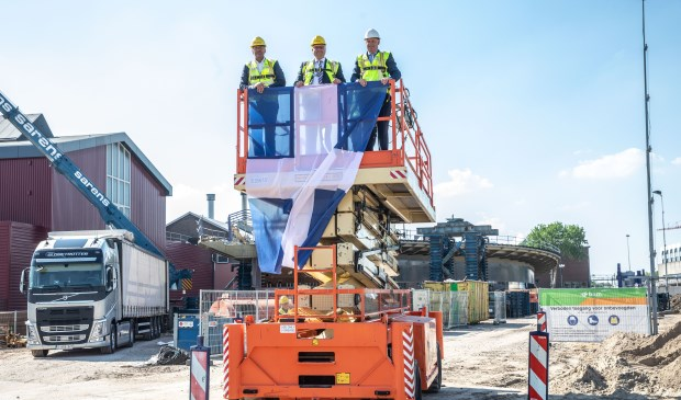 Met het bevestigen van de Zwolse vlag aan de hoogwerker op acht meter hoogte, markeren gedeputeeerde Bert Boerman, wethouder Ed Anker en Allart Maijers (projectmanager bij ProRail) op maandagmiddag 14 mei de hoogte van de nieuwe busbrug van Zwolle. (foto: Frans Paalman)