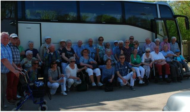 De groep bewoners van de Waard voor de bus die Ban Bouw B.V. uit Nuenen voor hen sponsorde. Met die bus reisde de groep af naar Hilvarenbeek en reed het gezelschap zelfs dóór het safaripark Beekse Bergen.