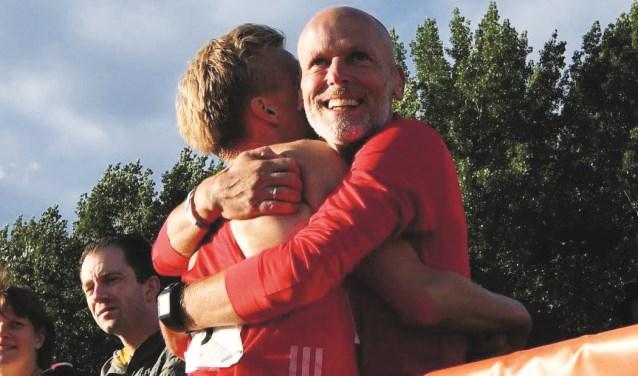 Titus Fierkens knuffelt Frank Futselaar na zijn onverwachte Nederlands kampioenschap op de tien kilometer in 2017.
