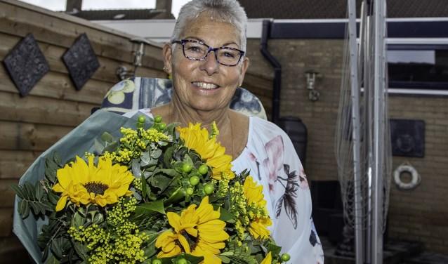 Ineke Derksen nog thuis en kort voor haar afscheid met de eerste mooie bos bloemen van de dag! Haar echtgenoot Henk is ook met pensioen gegaan, dus staat er een cruise naar Noorwegen op het programma. (foto: Wim Ham)