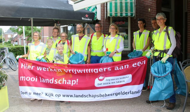 De dorpelingen van Stokkum poseren voordat ze aan de slag gaan met het opruimen van zwerfafval. Vierde van rechts wethouder Ruth Mijnen, die 'het startschot' gaf en meehielp.