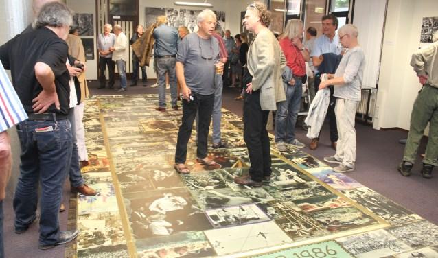 Joost Carlier, in het midden , vertelt aan één van de bezoekers over de foto's van weleer.