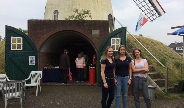 Julie de Goeij en Megan Schlief staan met Nicole van Andel, afdelingsleider bovenbouw HAVO, voor Molen De Volharding in Zeddam. De twee leerlingen van het Ludger College hielden er in het kader van de Molendagen een succesvolle streekproductenmarkt. (foto: Karin van der Velden)