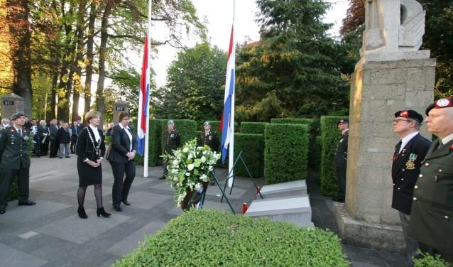 Burgemeester Bronsvoort en gemeentesecretaris Nekkers leggen een bloemenkrans bij het oorlogsmonument aan de Dijkstraat.