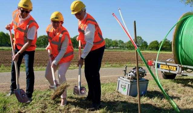 De wethouders Nijland (Aalten) en Frank (Oost Gelre) zetten samen met CIF-voorman Grootenboer de spade in de grond voor glasvezel in het buitengebied.