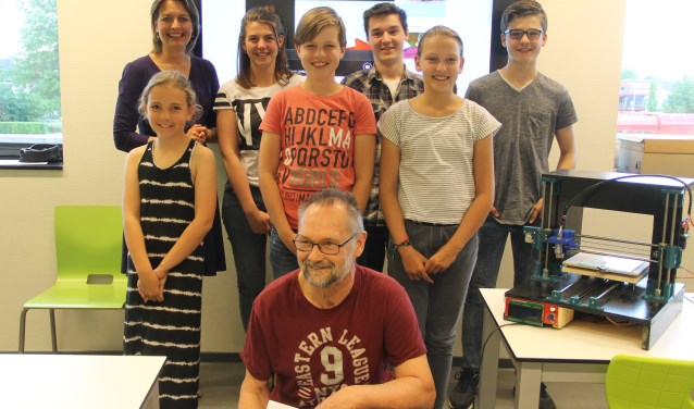 Wethouder Ilse Saris en Frits Sijbel met een aantal jeugdigde cursisten bij de 3D printer.