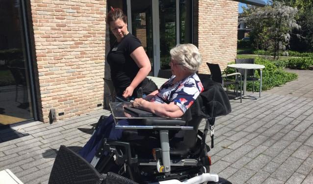 Terwijl Jo van der Voord vertelt over haar leven, legt verpleegster Sanne zorgzaam haar hand op de arm van Jo. Sanne: ' Ik ga nooit met tegenzin naar mijn werk.'