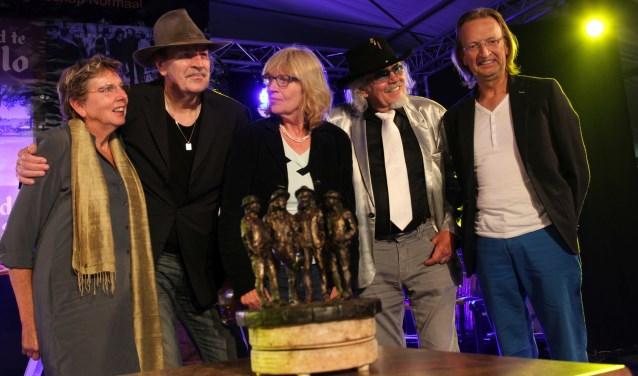De mannen van Normaal met hun echtgenotes bij een kleine versie van het standbeeld dat op Hemelvaartsdag onthuld wordt.