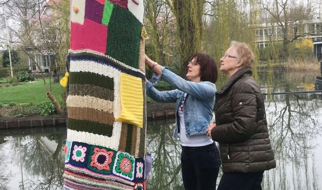 Liesbeth Vergeer en een van de bewoners leggen de laatste hand aan de 'boomkous'. (Foto: Isselwaerde)