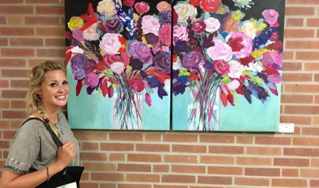 Claudia poseert voor een van haar schilderijen