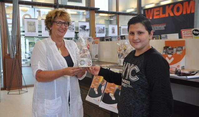 Het nieuwe bibliotheeklid én de aanmelder ontvangen een Zeeuwse Mok- 'Mokoke' met Zeeuwse bonbons én een tegoedbon. Links Ellen Kik, van de Bibliotheek Oosterschelde, rechts bibliotheeklid Wadee. FOTO: Anneke Flikweert