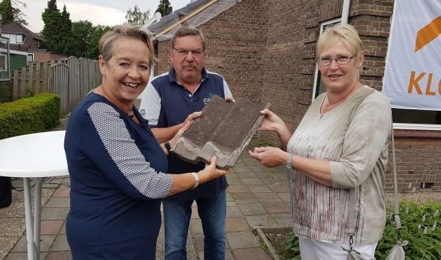 Marian Teer overhandigt de eerste dakpan aan de toekomstige bewoners van de Kolkakkerweg.
