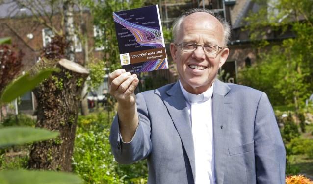 Vol trots toont pastoor Felie Spooren zijn vijfde boekje Spoortjes naar God. De voorzijde van het boekje is een ontwerp van Frank Maas. Foto: Jurgen van Hoof.