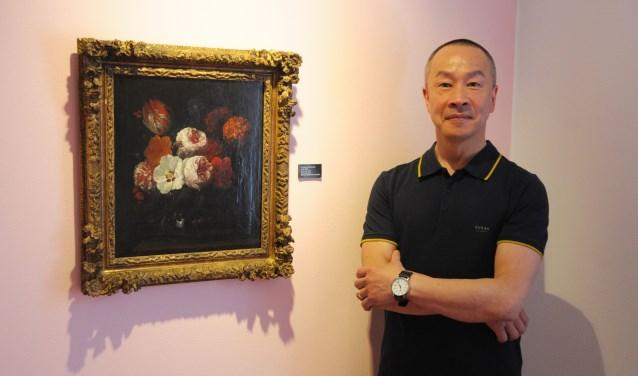 Galeriehouder Bruno Barat bij het schilderij 'Pioenen' van Nicolaas van Veerendael. Het is een van de werken waarmee de Bruno Barat Art Gallery bijdraagt aan 'Schot in de roos'. (foto: Voerman Museum Hattem)