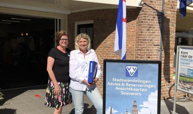 VVV-medewerkers Sylvia Landsheer en Annette Stout voor de VVV aan de Houtmarkt met de honderd arrangementen.