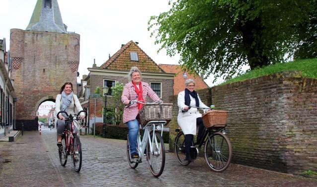 Wethouders Christianne van der Wal, José Oosthoek en Doret Tigchelaar (van links naar rechts) presenteren het boekje op de fiets.