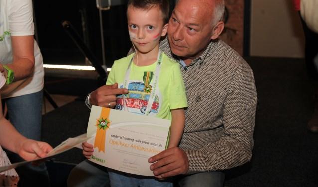 Dean (7) uit Oss met zijn onderscheiding en oorkonde. Hij kreeg die blijk van waardering voor zijn ambassadeurschap voor Stichting Opkikker uit handen van oprichter Ruud Sliphorst, ook op de foto.
