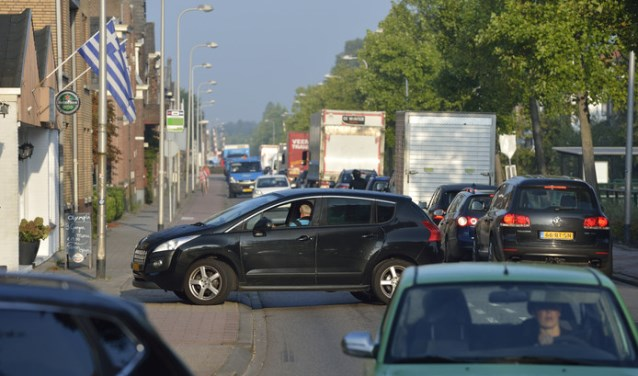 Met gevaar voor eigen leven probeert de ambulance, met sirene en zwaailicht en al, voorbij de file te rijden. Dat is niet eenvoudig in verband met het zeer drukke verkeer, welke vanuit de tegengestelde richting komt.