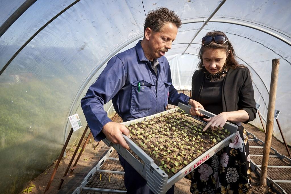 Henk Kerkers toont jonge groenten aan Anne-Marie Spierings