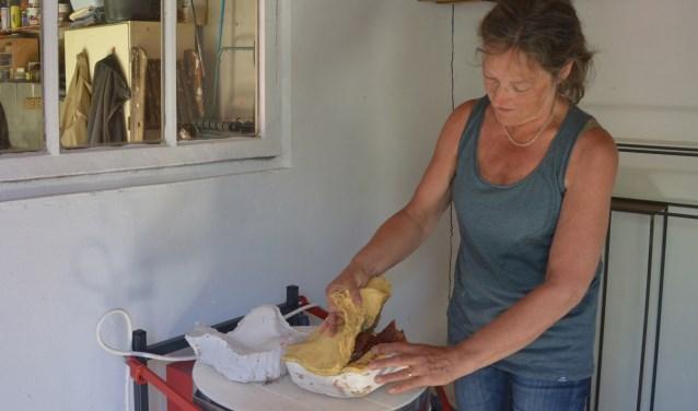 Jos laat in haar atelier in de tuin zien hoe de mal wordt gebruikt om een beeld te maken. Onder de mal de keramiekoven waarin veel van haar werk is gebakken. FOTO: Ben Blom