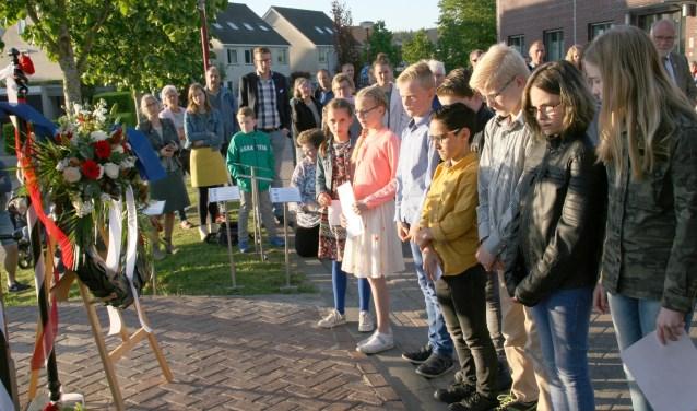 Schoolkinderen uit Elst leggen bloemen bij het herdenkingsmonument tijdens de dodenherdenking in Elst.
