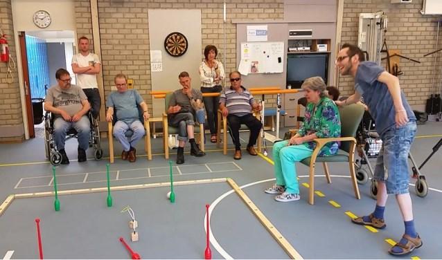 Client Theo (r) van Activiteiten Centrum Oosterschelde van Gors heeft de grootste lol met de robotbal Qbi. Het lijkt een simpel spelletje maar het vraagt behoorlijke concentratie. FOTO: CONNY DEN HEIJER