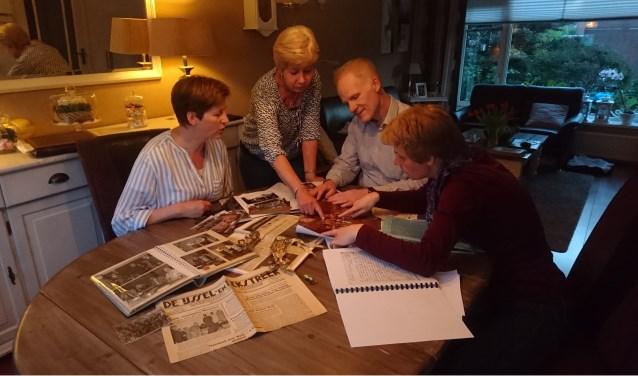 V.l.n.r. Mirjam, Ria, Guus en Lydia verwonderen zich over oude krantenknipsels en foto's van de muziekvereniging.