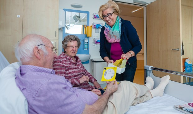 Vrijwilliger Vike Mulders laat een patiënt kennismaken met de collectie gesproken boeken.