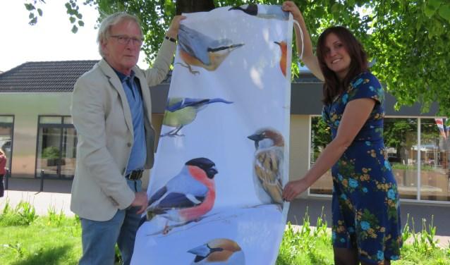 Gert Jan Koster en Ellen Bouter met een van de nieuwe banieren met daarop het schilderij 'Bennekomse vogels' van Elwin van der Kolk. Deze week worden de nieuwe banieren van 25 verschillende Bennekomse kunstenaars opgehangen in het centrum van Bennekom.