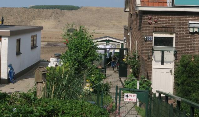 Een hoge wal scheidt de woningen aan de Rijksstraatweg van het bedrijventerrein Nieuw Reijerwaard. Op deze plek komt achter de wal de nieuwbouw van Bakker Barendrecht. (foto GvS)