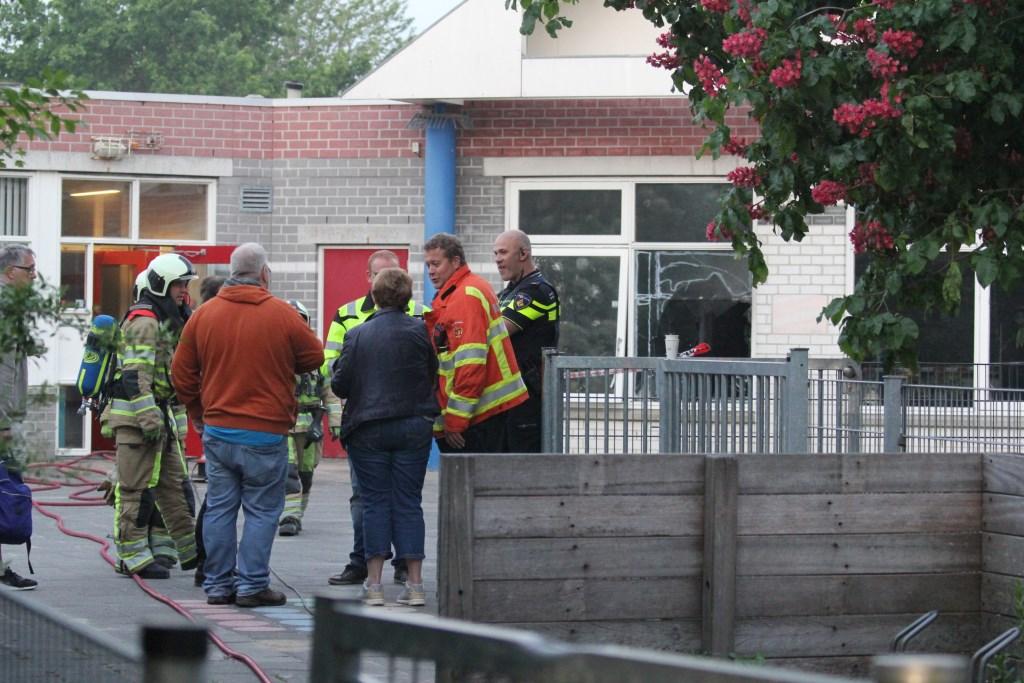 Bij daglicht komen mensen van de school samen met brandweer en politie de schade inventariseren. Op de achtergrond de vernielde ruit. Foto: ©2018 Jan-Peter Geertman © Persgroep