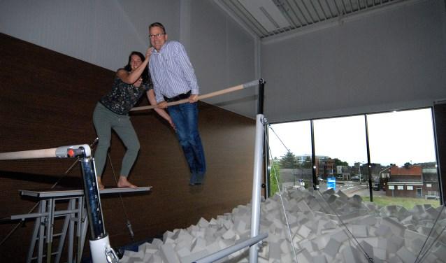 Denise de Vlam helpt Loek Smeets een handje op de brug die in de nieuwe turnhal boven de valkuil staat. Het raam geeft uitzicht op de Rochusrotonde. (foto: Tom Oosthout)