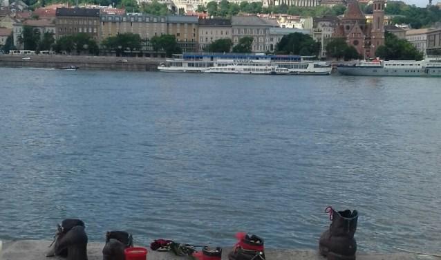 Deel van 40 meter lang Schoenenmonument aan de rivier de Donau in Boedapest . In de verte de Matthiaskerk.