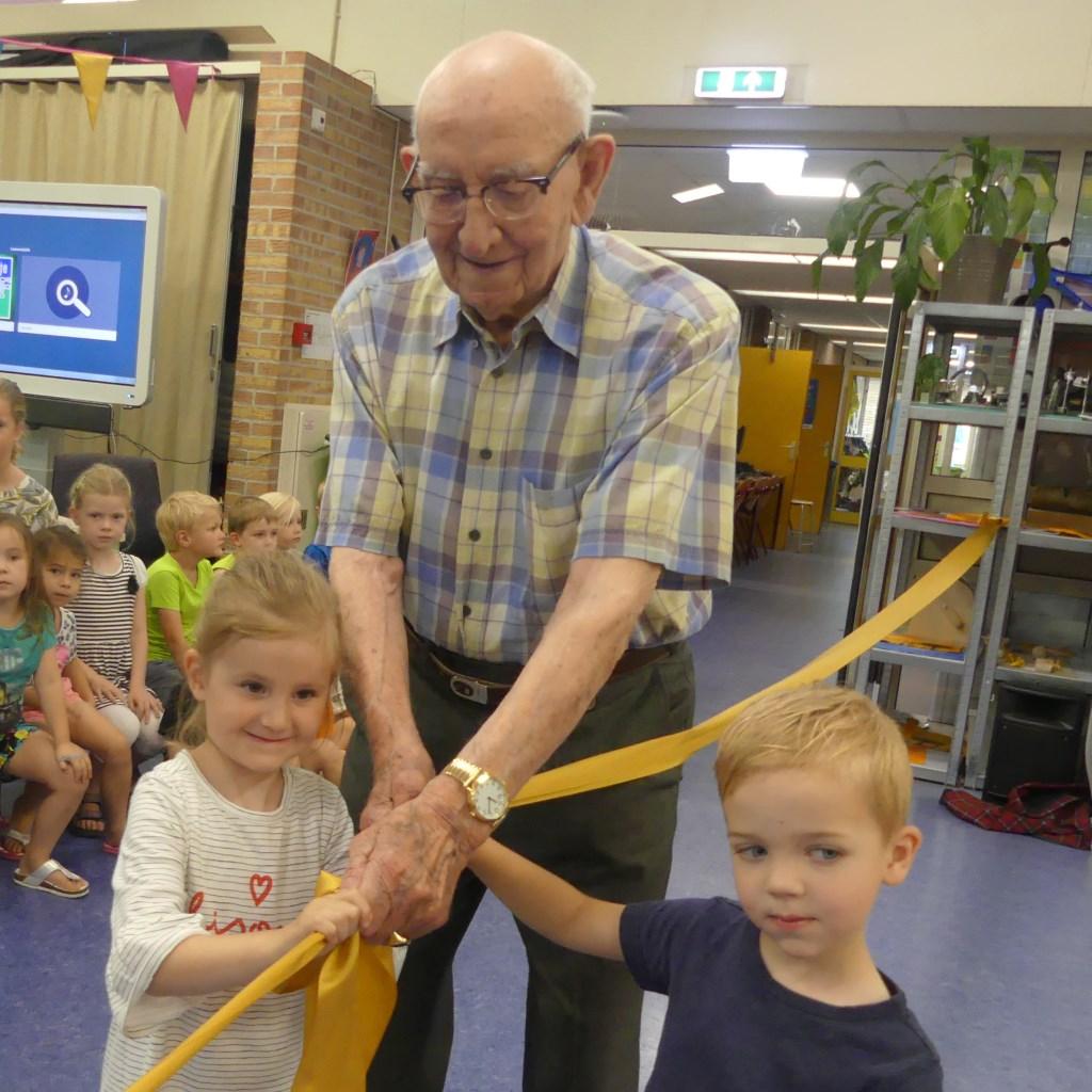 De heer Vernooij (oudste bewoner Weideheem) en twee kleuters knoopten twee linten aan elkaar en symboliseerde hiermee een succesvolle start van het  samenwerkingsverband. Eigen foto