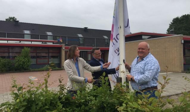 Examencoördinator Mieke van der Meer en locatiedirecteur Tjeert Jan Bosman hijsen de vlag in top. Foto: PR