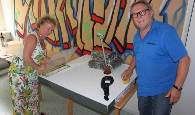 Ries van Atteveld (r) van het CSV en Charlotte Melssen van de buurtcommissie Holle Kamp druk aan het poetsen. Zo wordt het object 'Turf' weer toonbaar. (Foto: Martin Brink/Rijnpost)