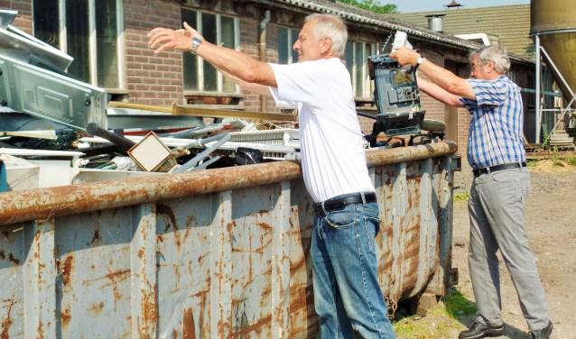 Teus Burger en Piet Hoogendam gooien nog wat oud ijzer in de bak. Het kan er nog net bij. De mannen hebben het er maar druk mee.