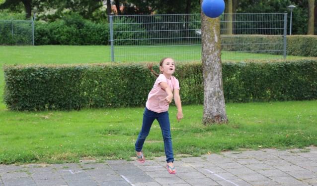 Kelsey springt met beide benen in de lucht als ze de bal gooit. Foto: Jan Hermens