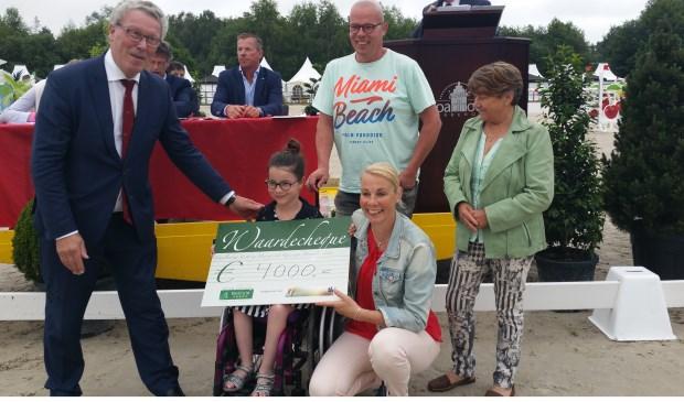 Ruiter Isa Verbeten krijgt een waarde cheque van vierduizend euro dat gaat naar een nieuwe buitenomheining goede voor manege het Roessingh.