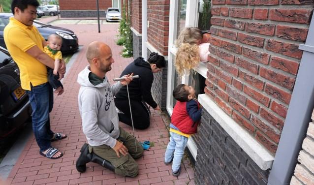 Onder begeleiding van Maarten Klein (voorgrond) ging Xiao Zhen Hu aan de slag met het raamtuintje van haar buren. Foto: Wendy Bakker