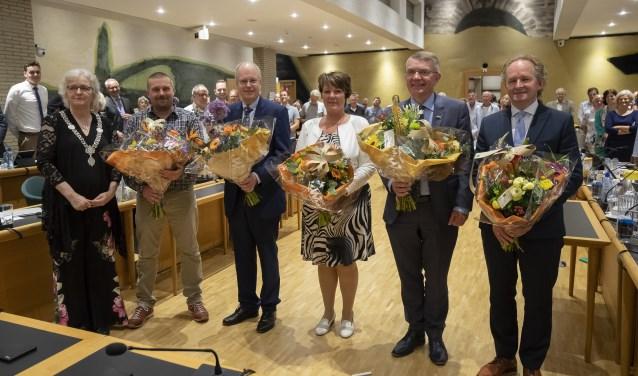 Het nieuwe college van B&W. Burgemeester Anny Attema (links) heeft de wethouders Henk van Os, Volbregt Smit, Cora van Vliet, Peter Meij en Marten Japenga in de bloemetjes gezet. (foto Gem. Ridderkerk)
