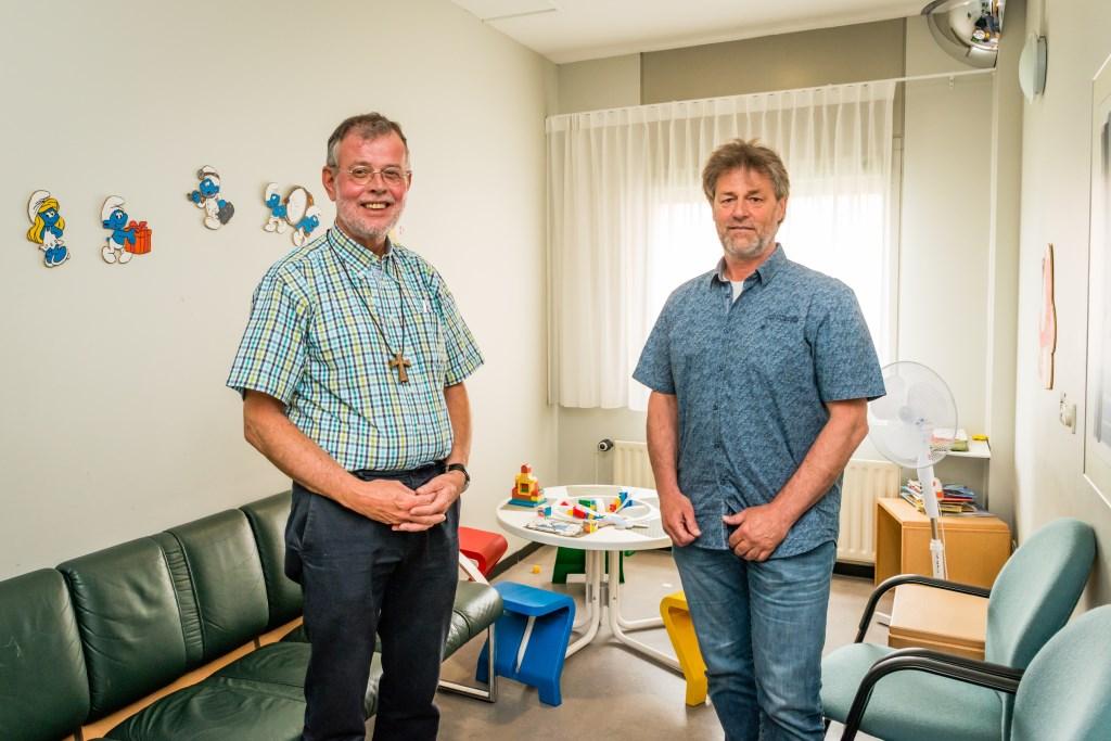 Pastor Jan Lange en Luc Zandstra, hoofd van bibliotheek, onderwijs en sport (rechts), gaan over de Ouder-Kindprojecten in PI Alphen. Zij poseren in de familiekamer van de gevangenis.  Foto: Bram Corstjens © Persgroep