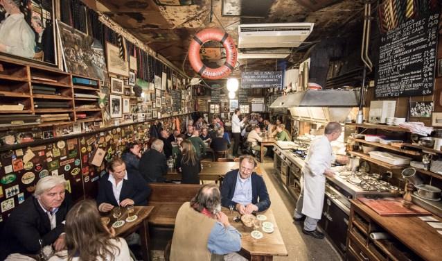 'Hier zit al jarenlang bekend en minder bekend Rotterdam, zij aan zij aan lange tafels, op harde houten banken en stoelen, die in het zaagsel staan.'