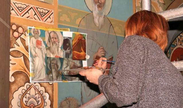 Een studente hertekent de afbeelding op de muur van de kerk. Foto: Henk van Dijk.